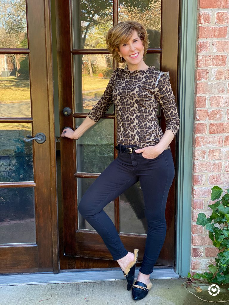 woman wearing kell parker leopard print ruffle neck sweater black jeans black faux fur lined faux leather black mules