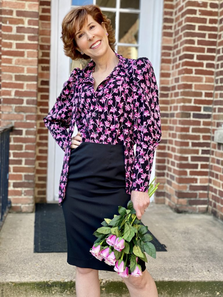 over 50 woman wearing target floral blouse and holding pink roses standing on steps