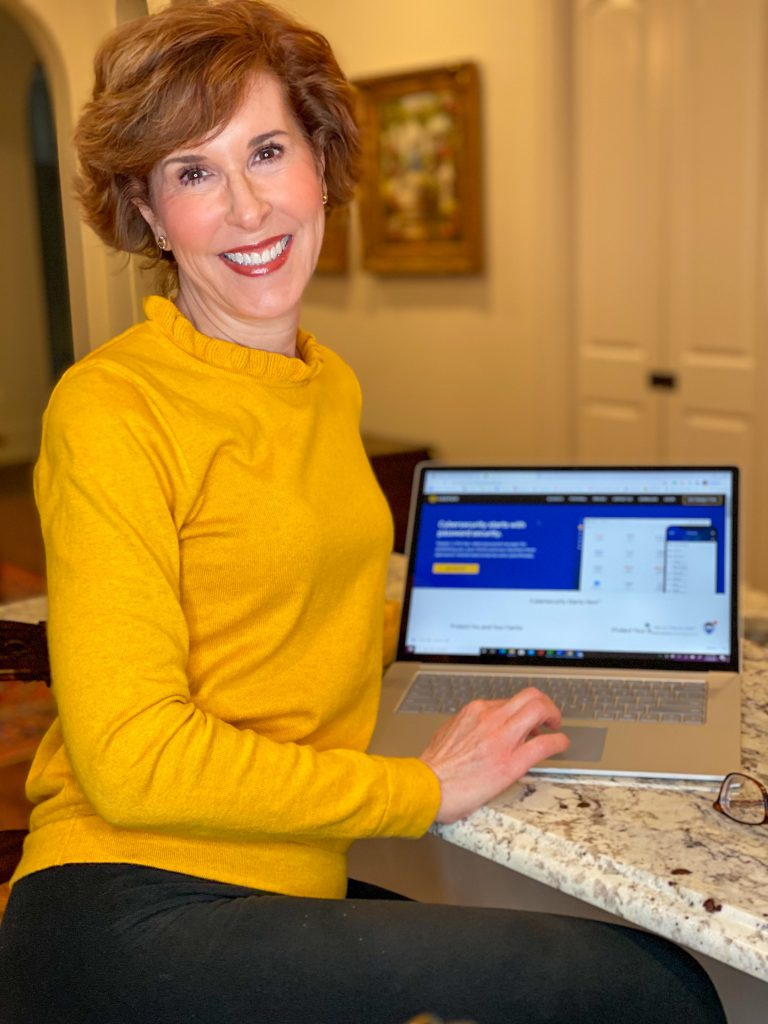 woman over 50 wearing yellow sweater with her laptop showing staying safe online with keeper security