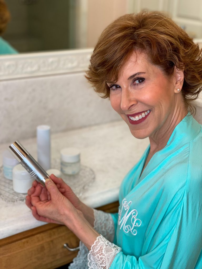 woman over 50 sitting at a bathroom counter in mint green robe looking at skincare ingredients in her skincare