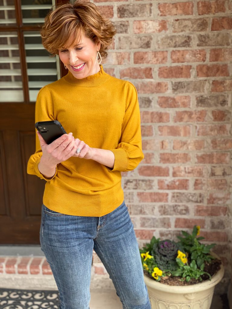 woman in Amazon The Drop gold ruffle neck sweater with 3/4 puff sleeves and jeans looking at her phone trying to keep her passwords organized