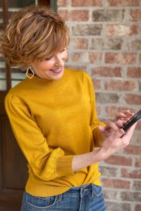 woman in Amazon The Drop gold ruffle neck sweater with 3/4 puff sleeves and jeans looking at her phone