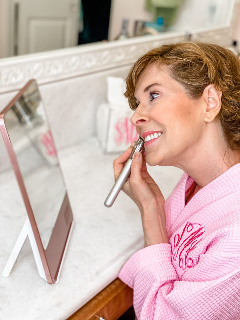 woman over 50 wearing pink monogrammed robe looking into a riki loves riki skinny makeup mirror and applying hoola matte bronzing powder