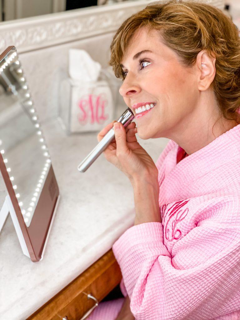 woman over 50 wearing pink monogrammed robe looking into a riki loves riki skinny makeup mirror and applying hoola matte bronzing powder