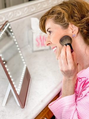 woman over 50 wearing pink monogrammed robe looking into a riki loves riki skinny makeup mirror and applying chanel rouge blush