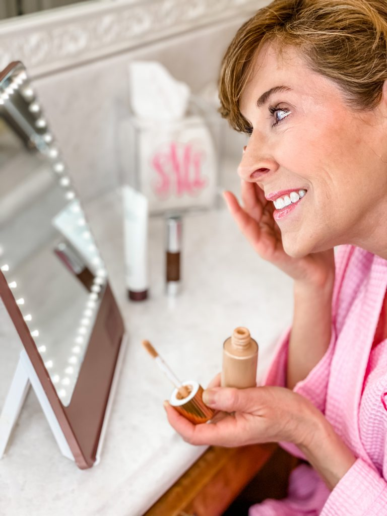 woman over 50 wearing pink monogrammed robe looking into a riki loves riki skinny makeup mirror and applying charlotte tilbury Hollywood Flawless Filter Primer & Highlighter