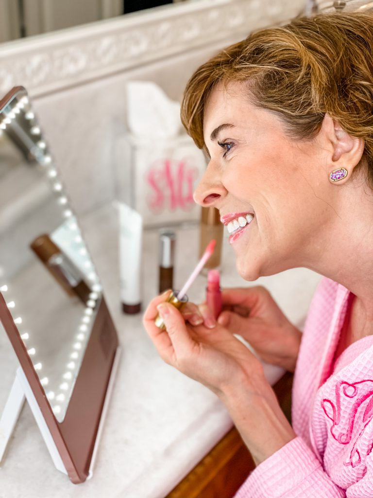 woman wearing pink waffle knit robe sitting at her vanity and applying city lips plumping lip gloss in sun diego and sharing tips for aging lips