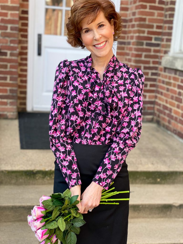 woman wearing a target tie neck blouse with a black pencil skirt holding pink silk roses