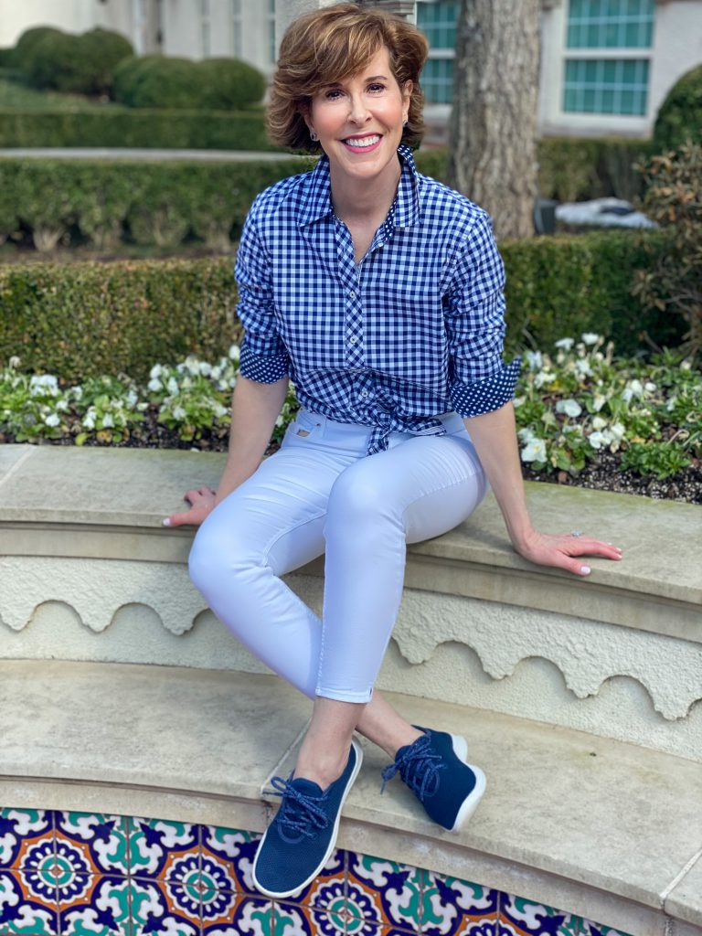 woman wearing talbots blue and white gingham shirt and white jeans with navy allbirds tree runner sneakers sitting on a wall