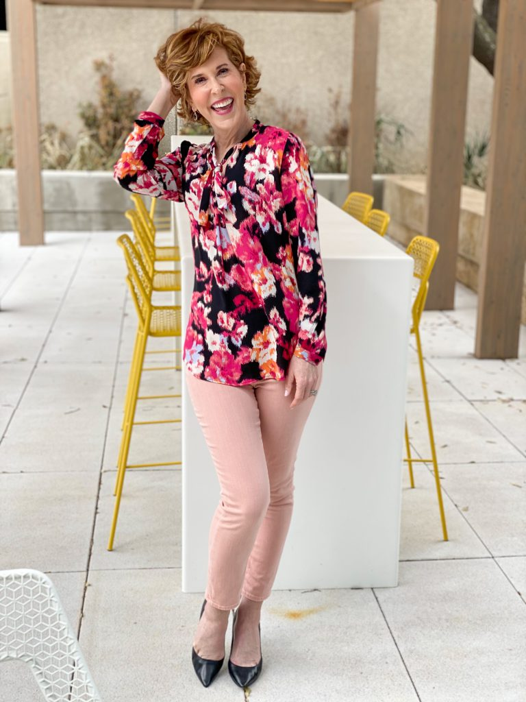 Woman over 50 wearing chico's floral tie-neck blouse with azalea jeggings and black pumps holding pink roses standing in front of a long table with yellow chairs