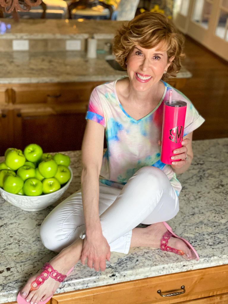 woman wearing tie dye shirt and white jeans with pink sandals holding a Marley Lilly pink tumbler sitting on a counter