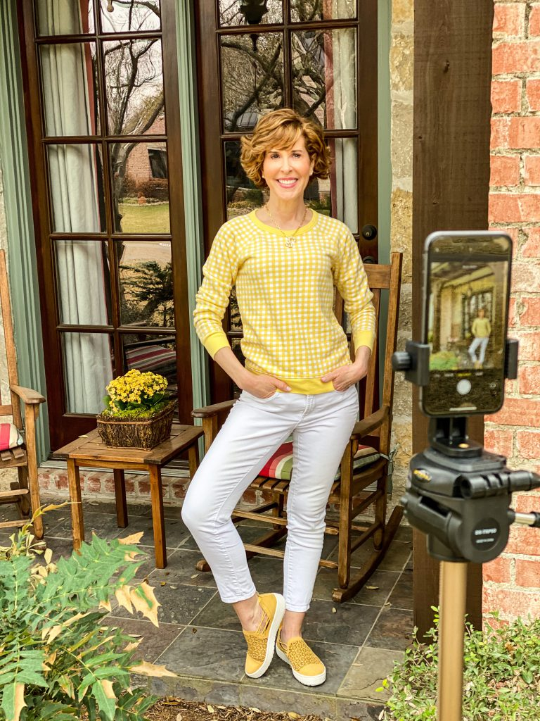 woman wearing draper james gingham and white sweatshirt and white jeans and yellow jambu sneakers standing on a front porch viewed through an iphone