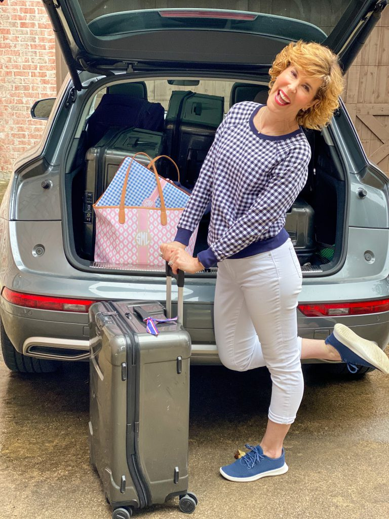 woman wearing draper james navy and white gingham sweatshirt and white crop jeans with navy allbirds tree runners standing with luggage behind a car with the trunk up