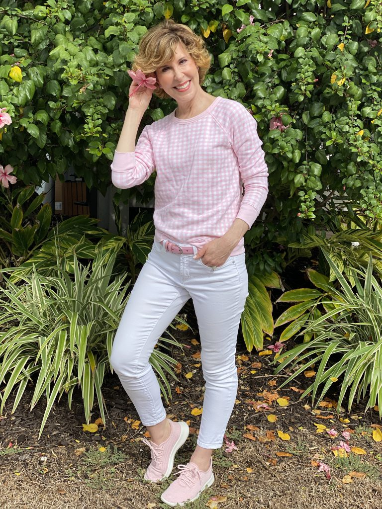 woman wearing draper james pink and white gingham sweatshirt and white jeans standing in front of bushes with a flower in her hair