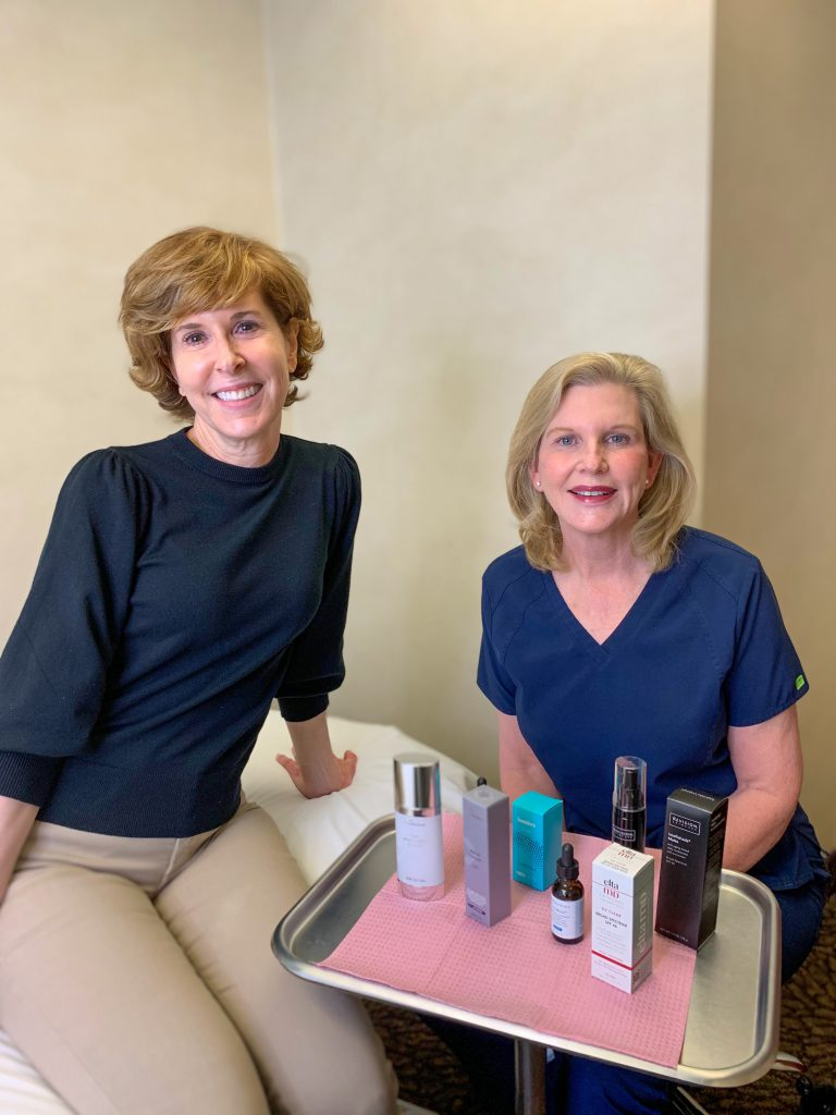 woman sitting with dermatologist dr lori stetler in front of a tray of the best skincare products for women over 50
