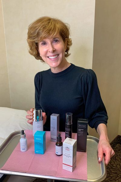 suzy mighell sitting in front of a tray holding the best skincare products for women over 50