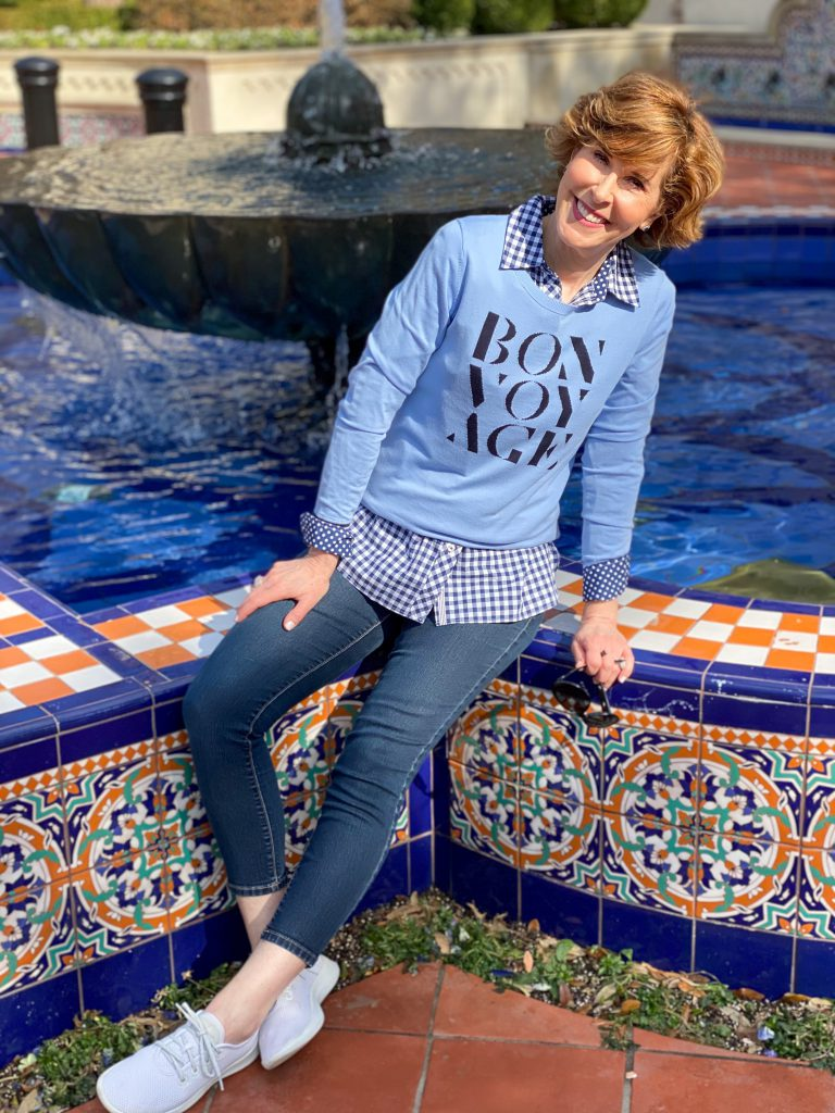 over 50 woman wearing Talbots blue bon voyage sweater over a blue and white gingham button down with jeans and sneakers sitting on the edge of a colorful fountain