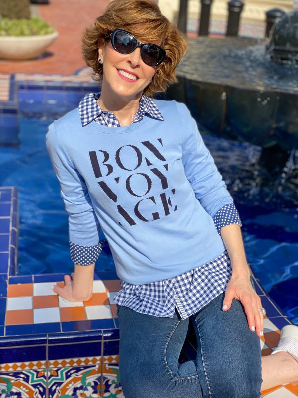 over 50 woman in sunglasses wearing Talbots blue bon voyage sweater over a blue and white gingham button down with jeans and sneakers sitting on the edge of a colorful fountain