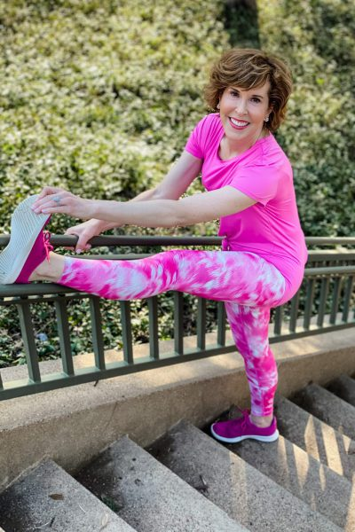woman aging well over 50 wearing pink zella workout leggings and tee stretching on a staircase