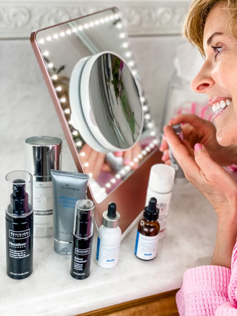 woman over 50 dressed in pink robe surrounded by medical grade skincare applying skincare products in white bathroom looking into rose gold riki loves riki skinny mirror