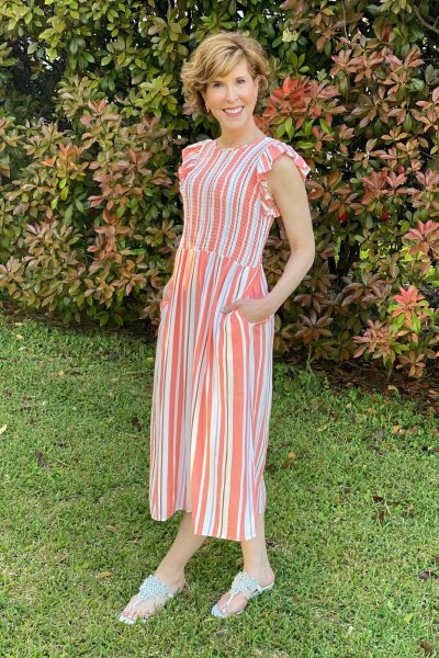 woman over fifty wearing target's a new day Sleeveless Smocked nap Dress standing in front of a nandina bush