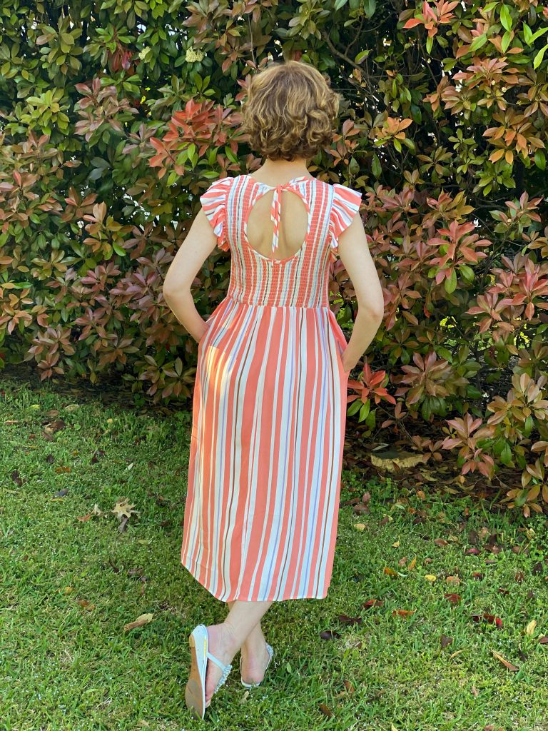 the back view of a woman over fifty wearing target's a new day Sleeveless Smocked nap Dress standing in front of a nandina bush