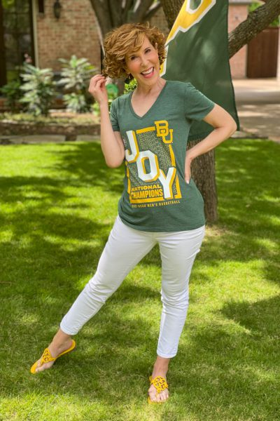 woman wearing green BU JOY tee and white jeans standng in a front yard