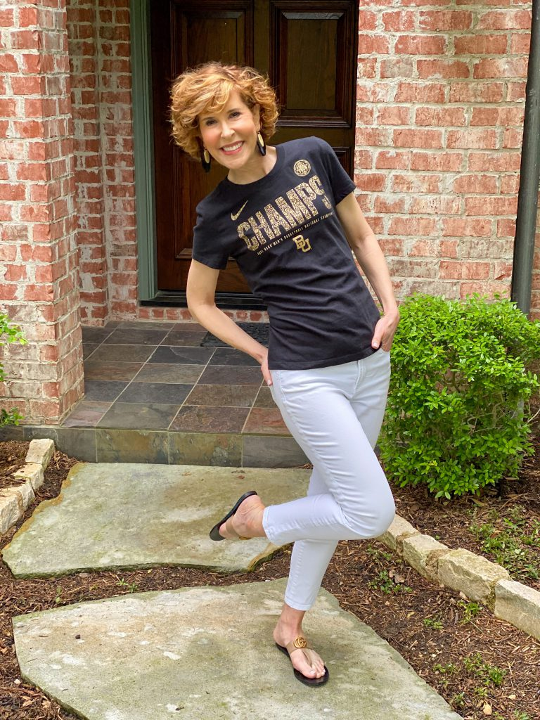 woman wearing black CHAMPS tee and white jeans standing on one foot in her front yard