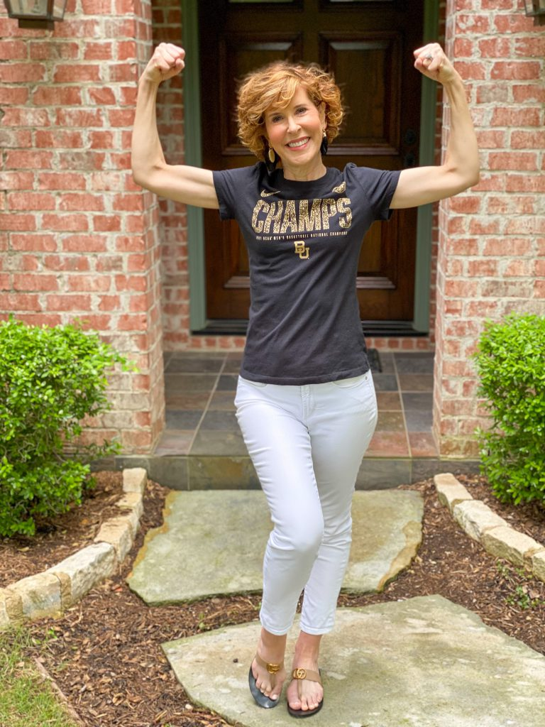woman wearing black CHAMPS tee and white jeans standing in her front yard flexing her muscles
