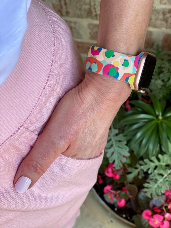 woman with hand in pocket of pink pants showing multicolored apple watch band
