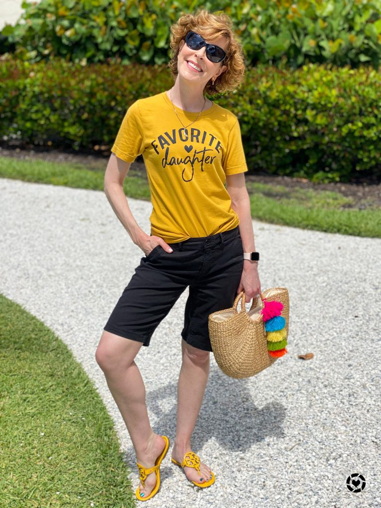 woman wearing yellow favorite daughter graphic tee and black bermuda shorts carrying cabana life live bright bag and standing on a white shell path