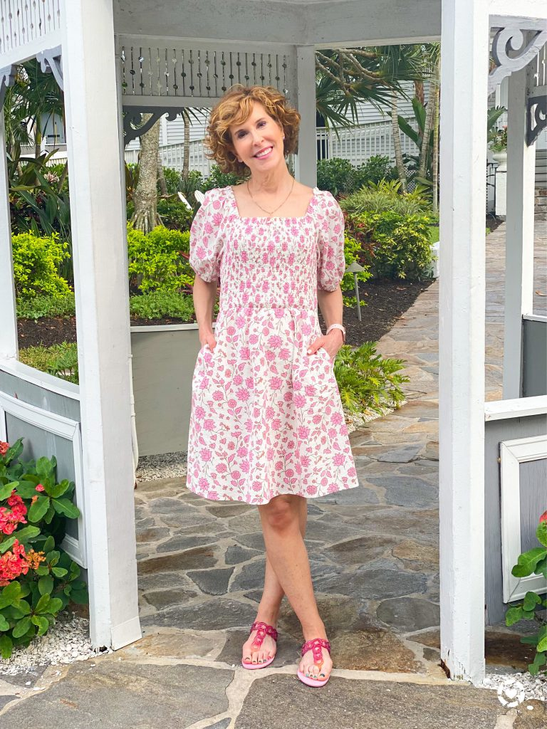 woman over 50 standing in a white and gray gazeebo wearing a Target Floral Print Puff Elbow Sleeve Smocked Dress - Universal Thread and pink big chain link jelly sandals by melissa