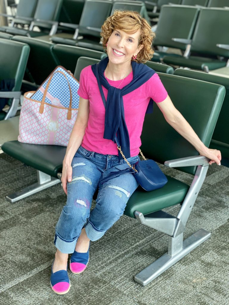 woman wearing nydj distressed Clean Monet Marilyn Straight Ankle Jeans a hot pink tee and a navy sweater around the neck with j.crew factory navy blue and pink espadrilles sitting in an airport waiting area