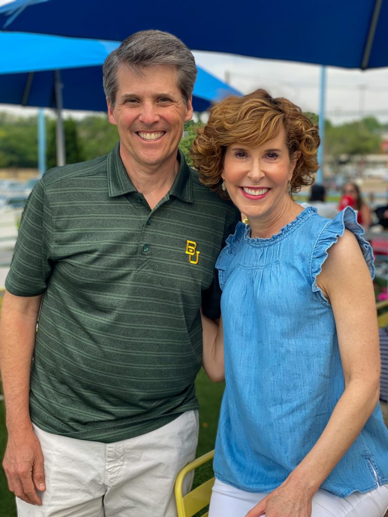 woman wearing chambray old navy ruffle sleeve and ruffle neck sleeveless top and husband wearing baylor university polo shirt standing on a restaurant patio