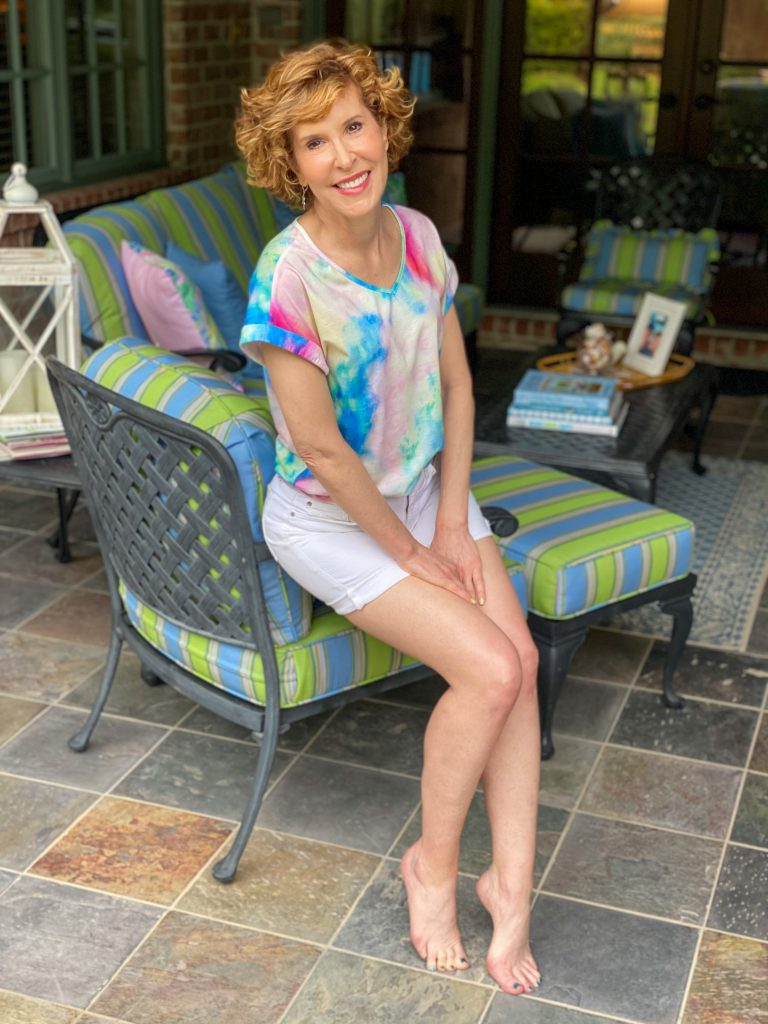 woman over 50 wearing tie die tee and white shorts sitting on the arm of a chair with her back patio behind her