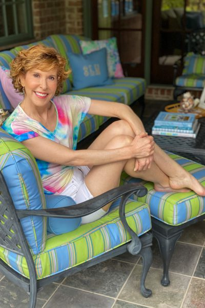 woman over 50 wearing tie die tee and white shorts sitting on a chair with her back patio behind her