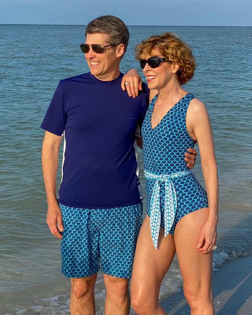 middle age couple in swimsuits posing on the beach
