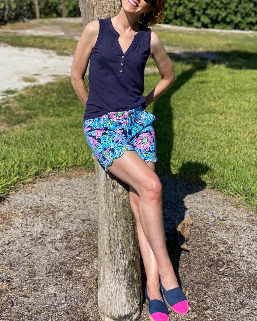 """woman wearing jcrew factory navy blue rattan earrings, lilly pulitzer navy blue essie tank top and 7"""" darci knit shorts learning against a palm tree."""