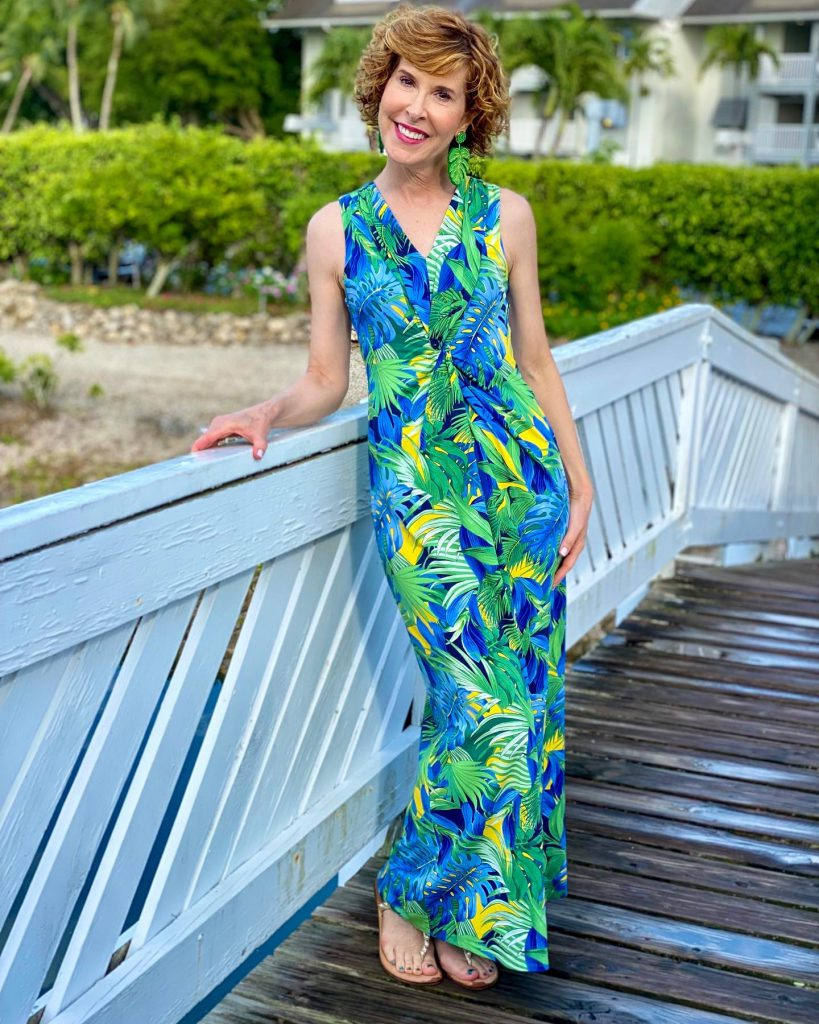 woman over 50 tommy bahama Hot Tropic Maxi Dress and jcrew factory palm earrings posing on a white bridge in a tropical location