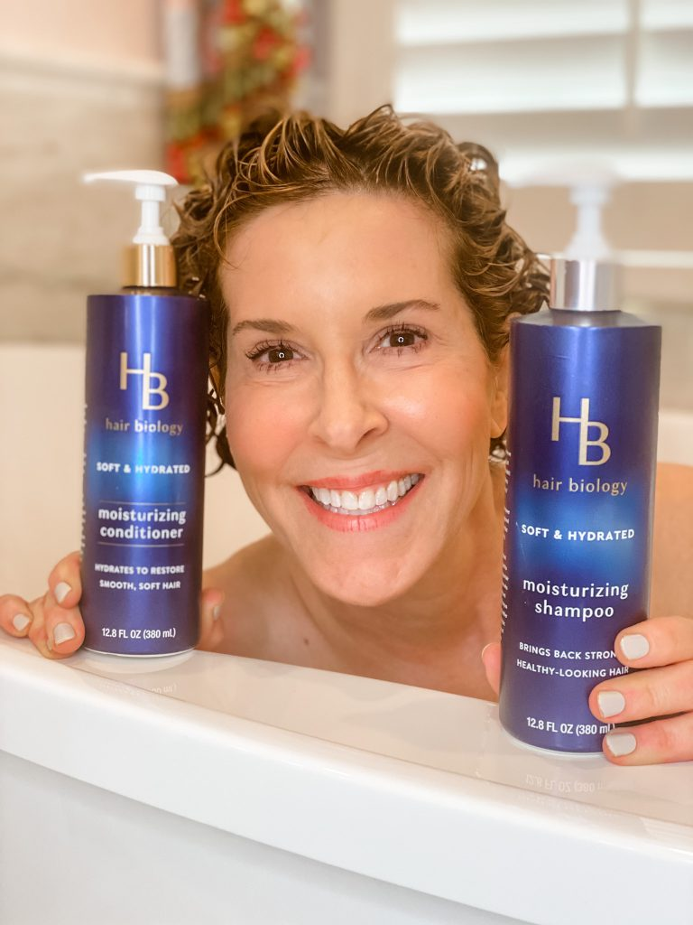 woman with wet hair peeking out of the tub with two hair biology products
