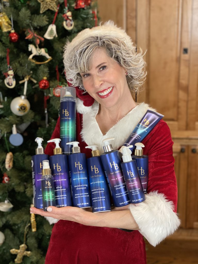mrs claus holding the entire hair biology line