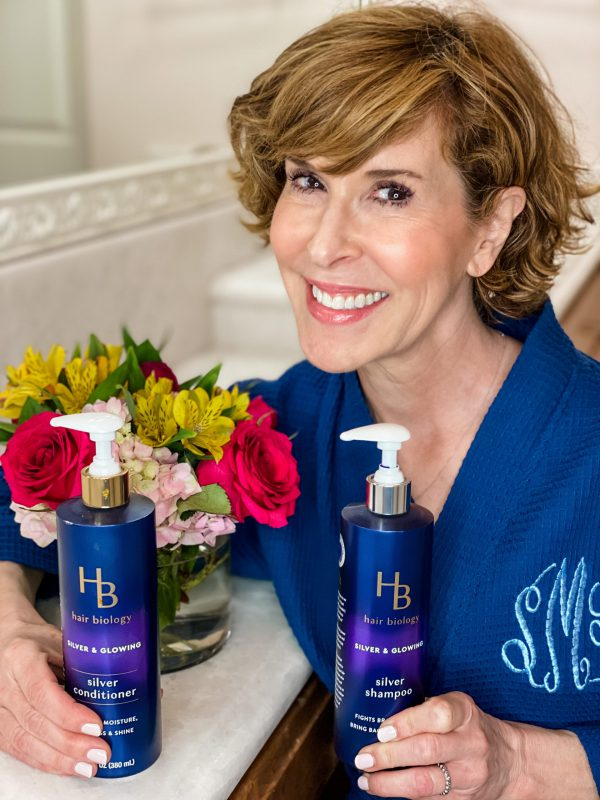 woman in blue robe with hair biology products and a bouquet of flowers behind her