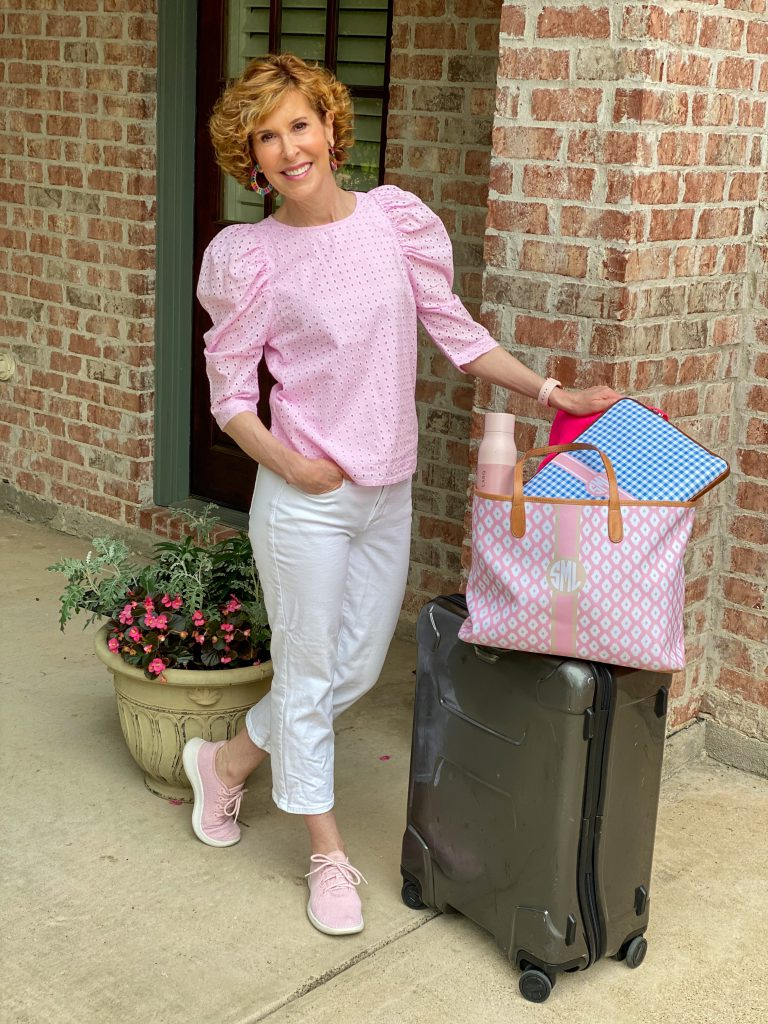 woman wearing pink eyelet top and white jeans standing by a suitcase getting ready for travel