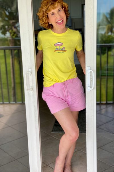 woman wearing yellow life is good tee and pink shorts standing in
