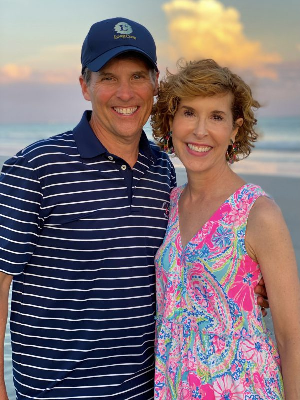 middle age man and woman on beach man wearing striped polo shirt woman wearing lilly pulitzer dress