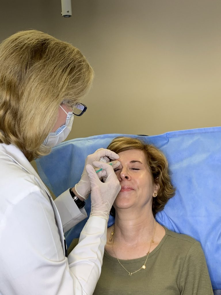 woman over 50 wearing green dress receiving botox injections from dr. lori stetler of dallas center for dermatology and aesthetics