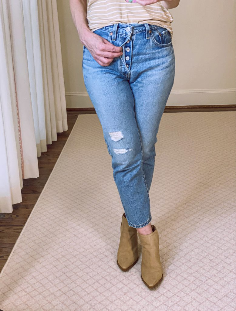 woman showing button fly in mom jeans