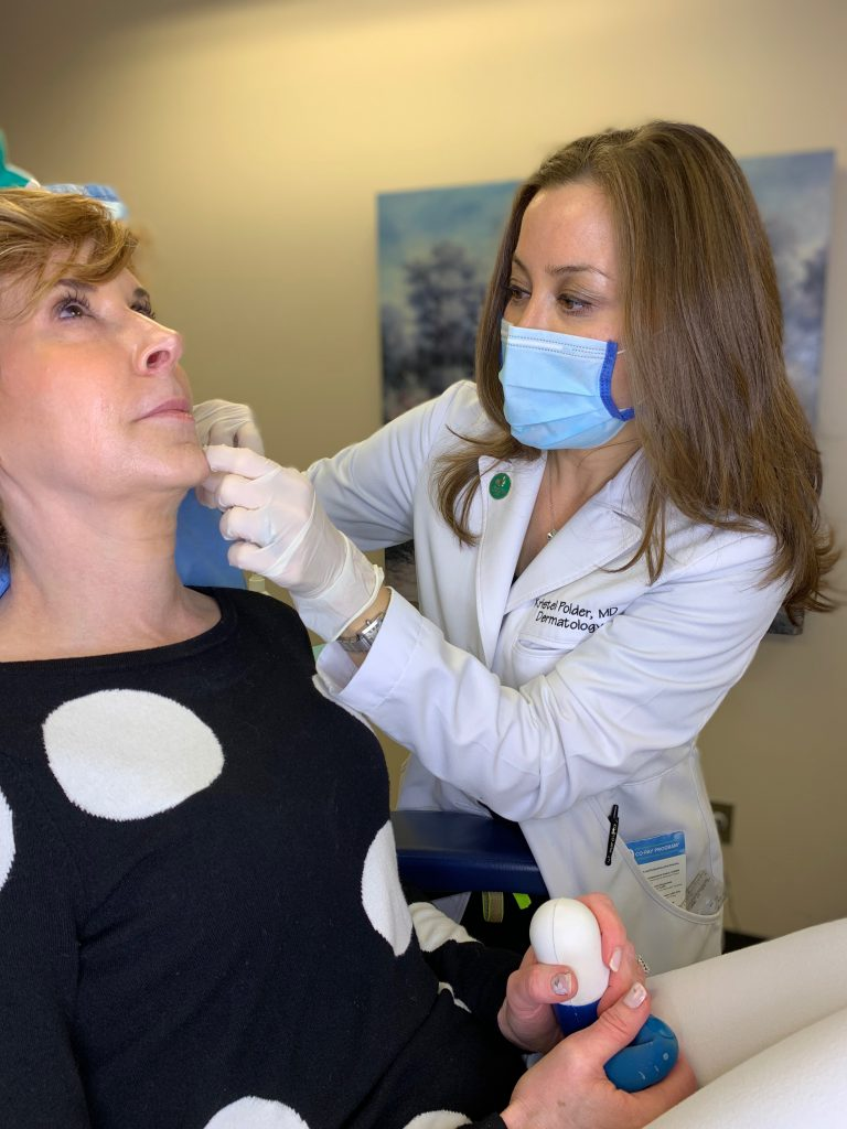 dr kristel polder from the dallas center for dermatology and aesthetics performing dermal fillers on a woman over 50 wearing black and white polka dot sweater