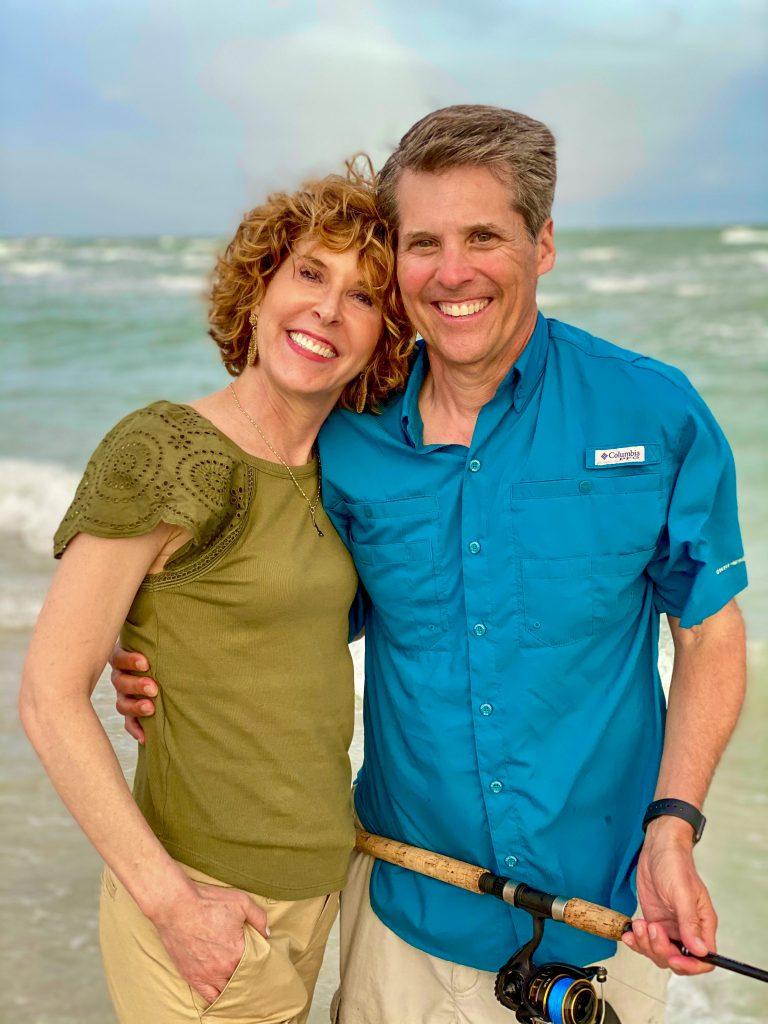 middle age couple on beach man wearing teal fishing shirt woman wearing sage green eyelet flutter sleeve shirt