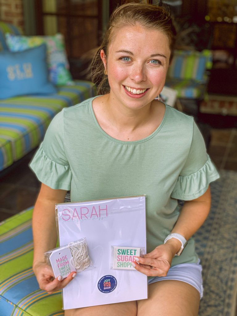 girl in green top holding products from Joy Creative Shop